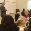 Photo of Chris Steinhardt '91 in classroom with SUNY Plattsburgh Students