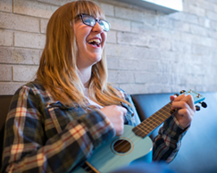 Photo of SUNY Plattsburgh student playing ukulele