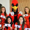 Photo of SUNY Plattsburgh students sitting with Burghy holding Burghy Bucks