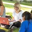 Photo of students studying on the grass.