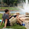 Photo of SUNY Plattsburgh students relaxing in front of Hawkins Hall pond