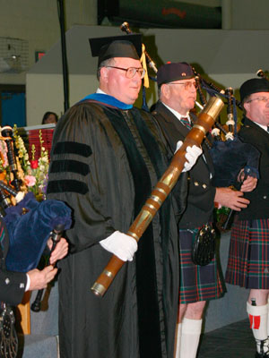 Dr. Charles Zinser, the most senior member of the faculty, carries the mace.