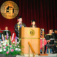 Photo of students speaking at commencement lecturn, dressed in academic regalia