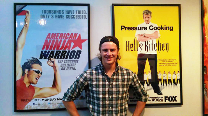 Photo of Trevor Ken standing in front of posters of television shows he has worked on while living in Los Angeles