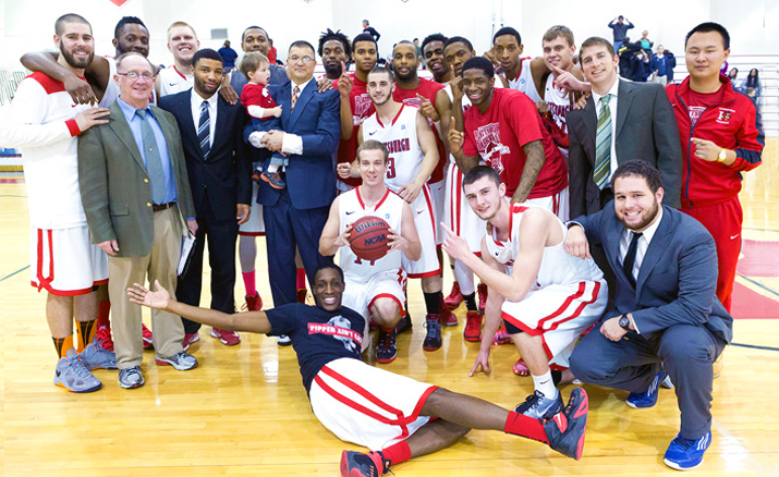Photo of Coach Tom Curle celebrating a victory with the men's basketball team.