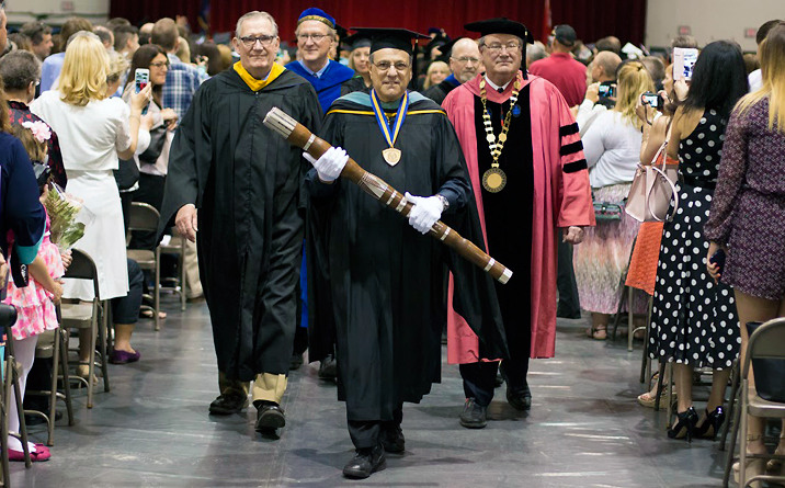 Photo of Tom Corigliano carrying the mace one final time at Spring 2016 Commencement