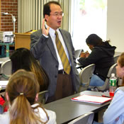 Photo of Dr. Kwangseek Choe talking to a group of SUNY Plattsburgh students