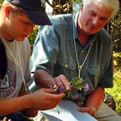 Photo of Ken Adams working in the field with student