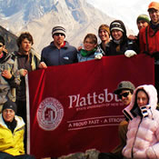 Photo of SUNY Plattsburgh students holding a school banner on a mountain top in Nepal