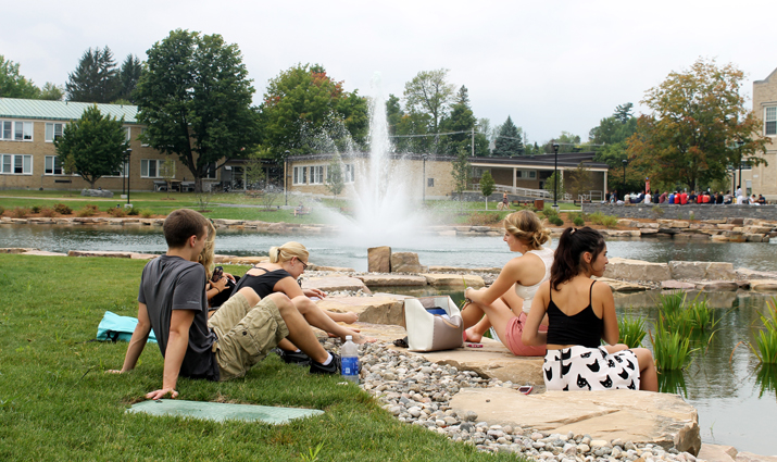 Photo of SUNY Plattsburgh students studying by the newly renovated Hawkins Hall pond.
