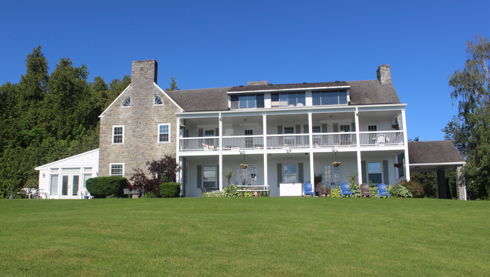 Photo of the Vaclour Inn taken from the front lawn, facing the lake.