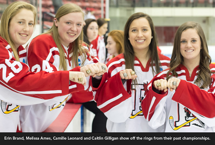 Photo shows Erin Brand, Melissa Ames, Camille Leonard and Caitlin Gilligan showing off the rings from their past championships.