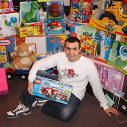 Photo of SUNY Plattsburgh graduate student Brian Ensel, sitting on the floor, surrounded by toys