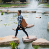 Photo of  SUNY Plattsburgh student walking in front of Hawkins Pond