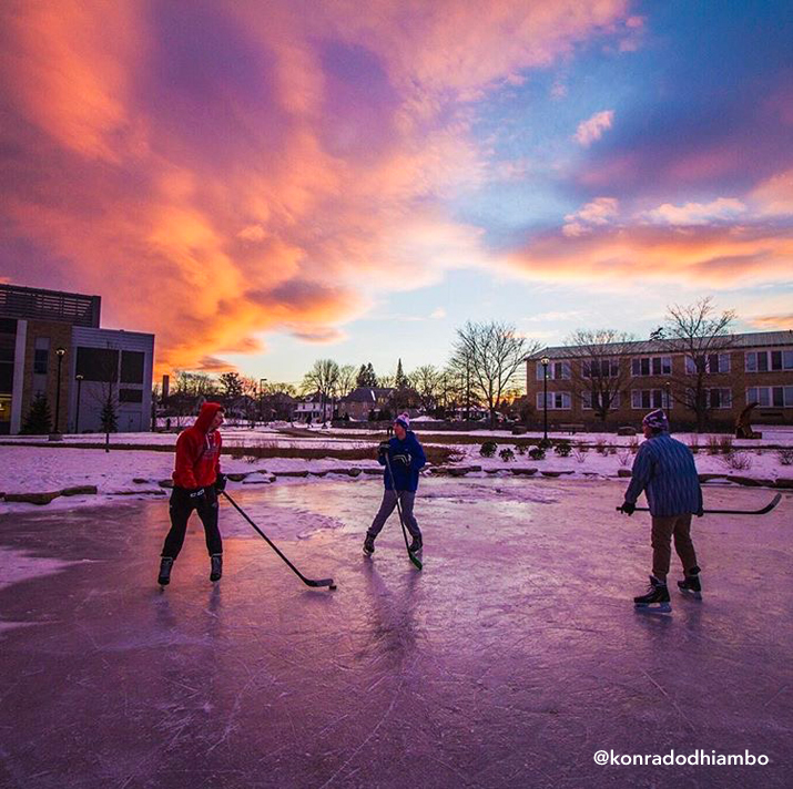 Photo of students playing pick-up hockey on the ice of frozen Hawkins Pond by konradodhiambo