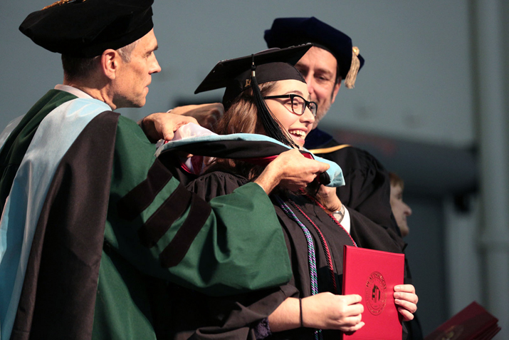 Student on stage recieving her diploma