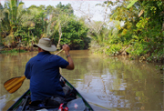 Photo of an EXP student paddling a canoe in a river in Southeast Asia
