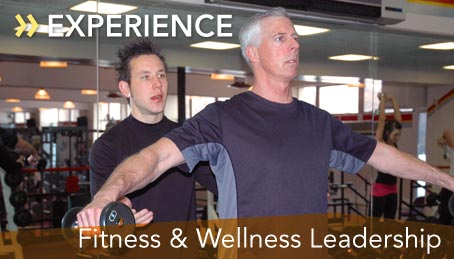 Photo of a student coaching a man lifting weights in the fitness center