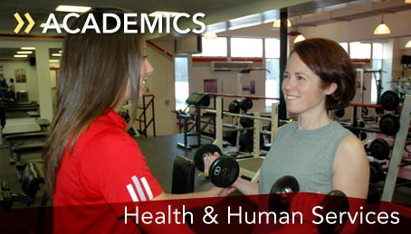 Photo of a student coaching a woman lifting weights in the fitness center
