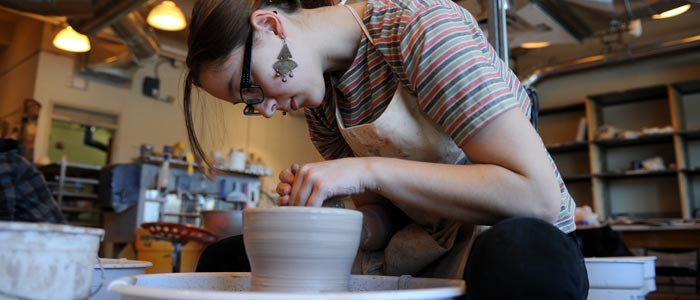 Photo of a student working at a pottery wheel
