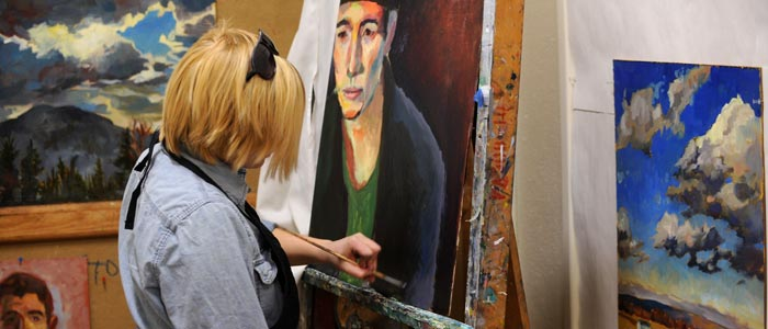 Photo of a student working on a painting in her studio