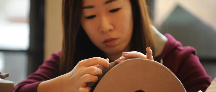Photo of a student working on a clay sculpture