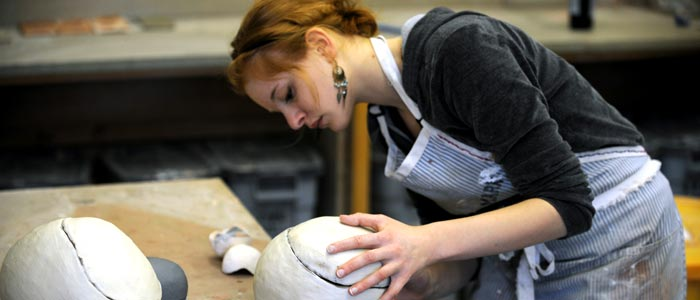 Photo of a student working on a sculpture in the studio