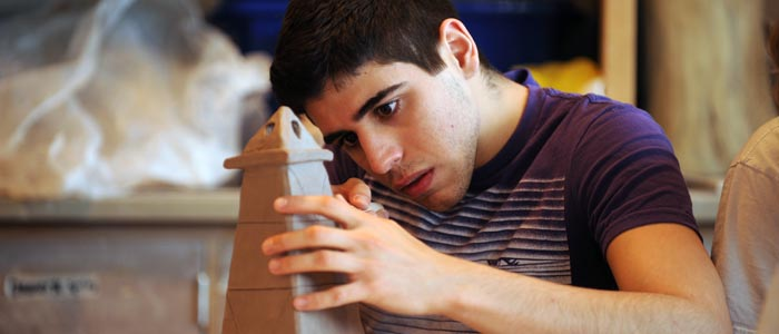 Photo of a student working on a clay scupture