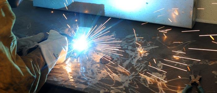 Photo of a student welding a metal sculpture