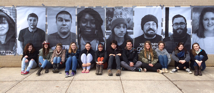 Students gathered under images from the guerilla photography project