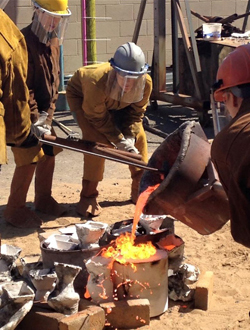Photo of students in the foundry pouring molten metal into a mold