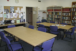 View of the furniture, which includes two conference tables, chairs, microwave and well-stocked bookcases
