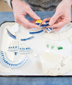 Photo of faculty piecing togher broken dishes found on a dig