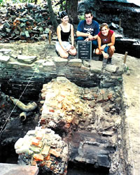 Three students proudly showing their completed excavation