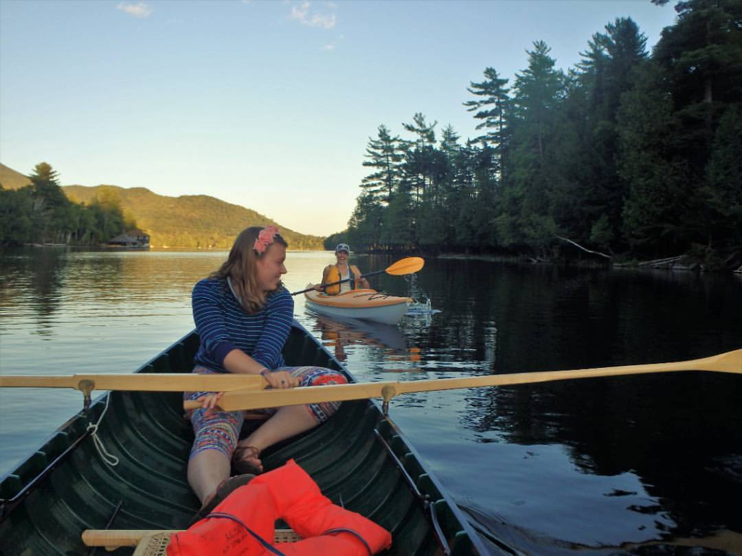 Photo of Steffaney Wilcox on the water rowing a canoe