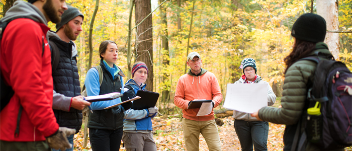 Photo of students listening to a professor in the woods