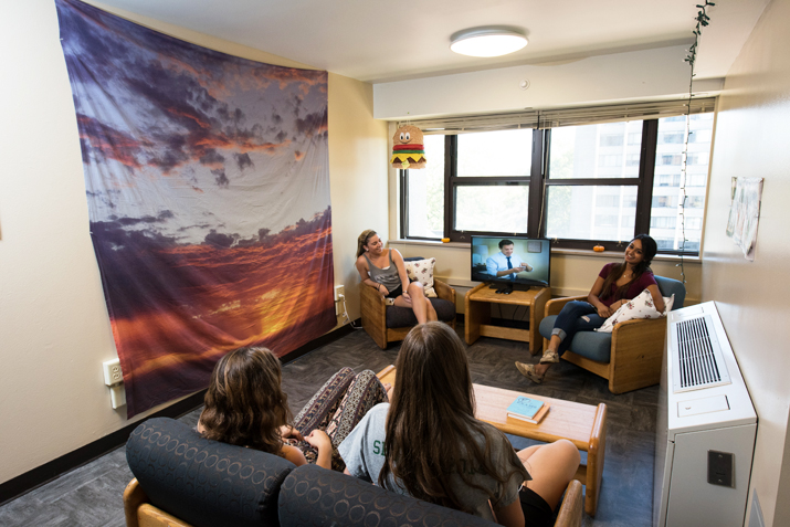 Students watching television in a dorm room.