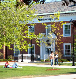 Photo of students studying in the grass, and walking on front of Macdonough Hall