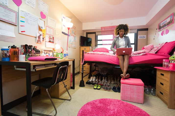 A student using her laptop in a dorm room.