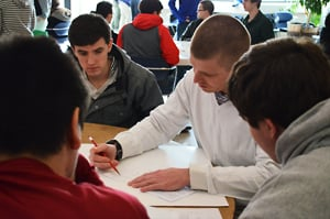 Tim Mulligan, a mathematics teacher at Plattsburgh High School, discusses a contest problem with some of his students. Photo by Jessica Karszen