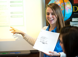 Photo of a student teacher working with teenagers in a classroom