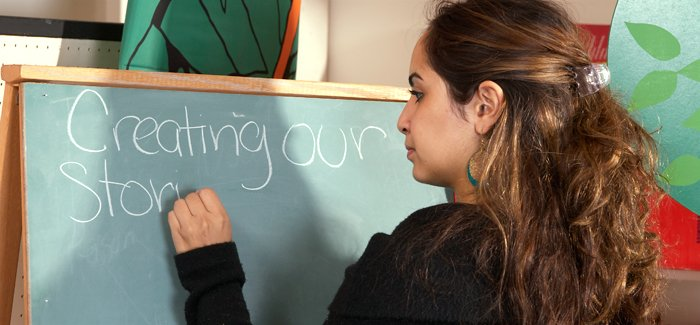 Photo of a student teacher writing on a chalk board