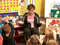 Photo of a teacher working with a group of small children