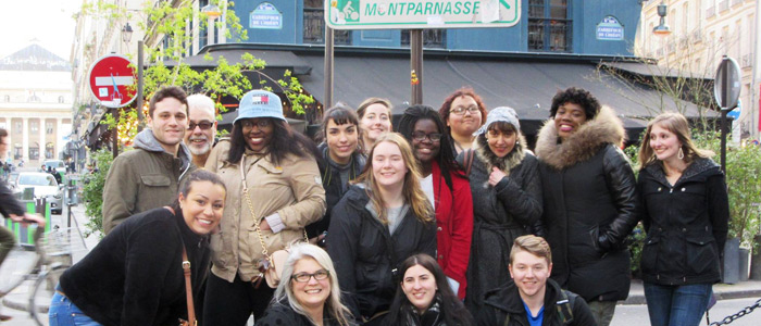 Photo of English majors posing under a street sign on a trip to Paris