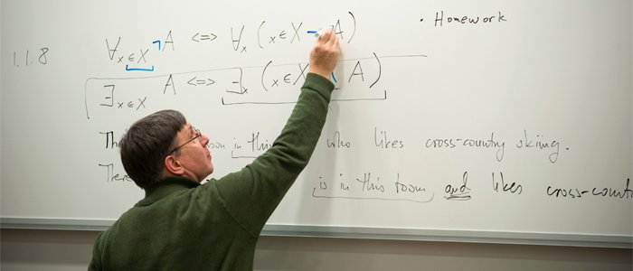 Photo of Dr. Jan Plaza writing on the white board