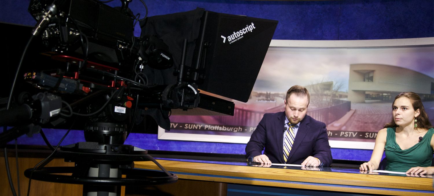 Two broadcast journalism students on the set of Studio A shooting a News Brief segment.