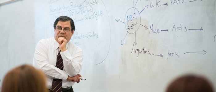 Photo of Dr. Mohamed Gaber standing in front of a diagram-filled white board and listening to a student's question in class