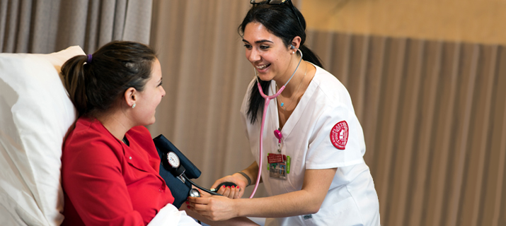 Photo of a nursing student working in a hospital setting with a patient