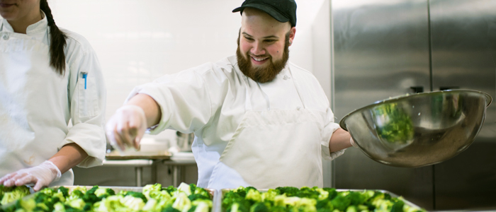 Photo of students seasoning broccoli in the professional kitchen