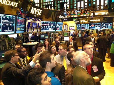 Photo of economics and finance students and Dr. Christopherson on the floor of the New York Stock Exchange